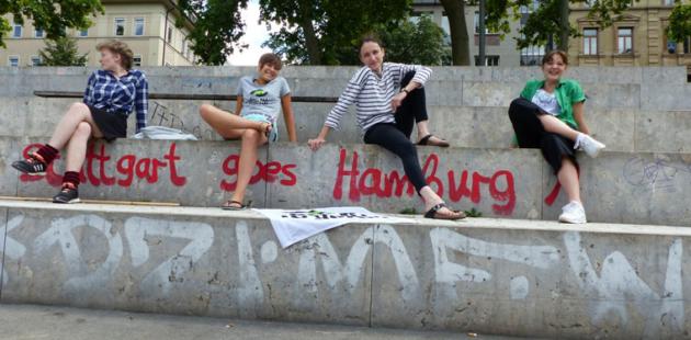 Vier Menschen sitzen in der Stadt auf einer großen Steintreppe