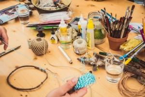 Basteltisch mit Garn, Pinseln und weiterem Zubehör